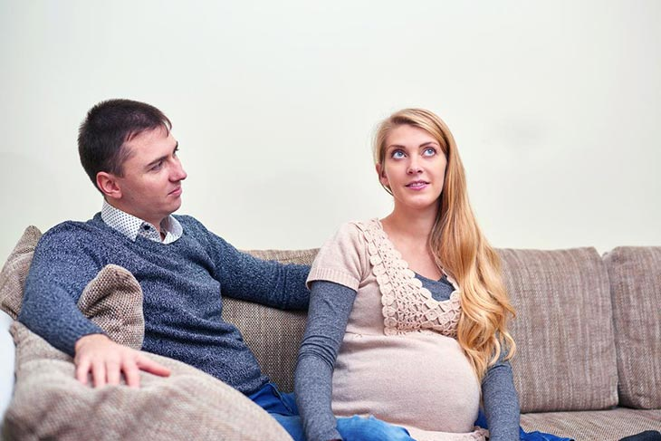 happy-pregnant-couple-sitting-on-sofa
